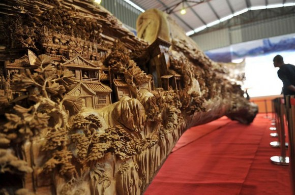 """A giant masterpiece has been recorded as the longest one piece wood carving in the world. And the time it took to get it officially recognised is also almost a record - after the exhibition hall where it is housed revealed it was actually crafted in Fujian province in southeast China nearly 1,000 years ago. Called """"Riverside Scene at Qingming Festival"""", it has only now been recognised by the Guinness Book of World Records as the largest single piece wood carving in the world. The work measure 12.286 meters long, and at the highest point is 3.075 meters. It is also 2.401 meters wide. It took artist Zheng Chunhui four years to complete and currently is stored at the Palace Museum in Beijing where it is recognised as a national treasure. A museum spokesman said: """"He was a master craftsman but sadly this is the only piece of his work to have survived. But nevertheless it is a remarkable piece. """"It gives a 3D snapshot of a period in the life of daily life of people of all ranks in the capital city of Bianjing (today's Kaifeng, Henan Province) during Qingming Festival in the Northern Song Dynasty. As such it is also a valuable historical witness, bringing the period to life in a way that a book or scroll never could. """"It's the next best thing to experiencing it in real life, showing rich and poor about their daily business. In fact there are 550 people in the carving."""""""